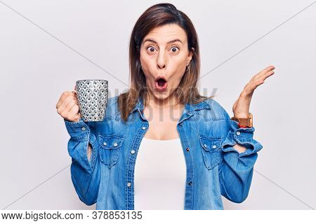 Young beautiful woman holding coffee scared and amazed with open mouth for surprise, disbelief face