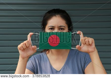 A Woman With Bangladesh Flag On Hygienic Mask In Her Hand And Lifted Up The Front Face On Dark Green