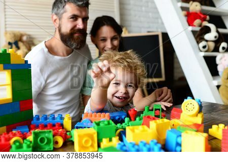 Young Family Spends Time In Playroom. Parents Watch Son