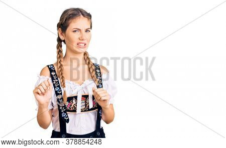 Beautiful caucasian woman with blonde hair wearing octoberfest traditional clothes disgusted expression, displeased and fearful doing disgust face because aversion reaction. with hands raised