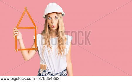 Beautiful caucasian woman with blonde hair wearing architect hardhat and holding tools scared and amazed with open mouth for surprise, disbelief face