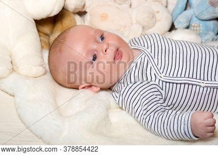 Baby Boy In Striped Bodysuit. Baby Lying On White Duvet