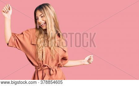 Beautiful caucasian woman with blonde hair wearing summer jumpsuit dancing happy and cheerful, smiling moving casual and confident listening to music