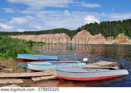 Three Boats Are Moored On The River Bank.high Bank, Rocky, Steep. Exposed Geological Rock, Which Is