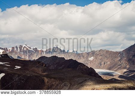 Atmospheric Mountain Landscape With Rocky Ridge With Snow And Glacier Tongue In Sunlight. Big Cloud
