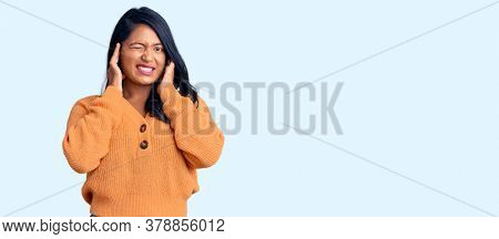 Hispanic woman with long hair wearing casual winter sweater covering ears with fingers with annoyed expression for the noise of loud music. deaf concept.