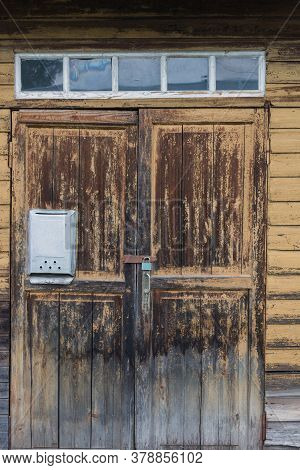 Old Wooden Door To The House. The Yellow Paint On The Door Exfoliated, Faded, Cracked. Empty Mailbox