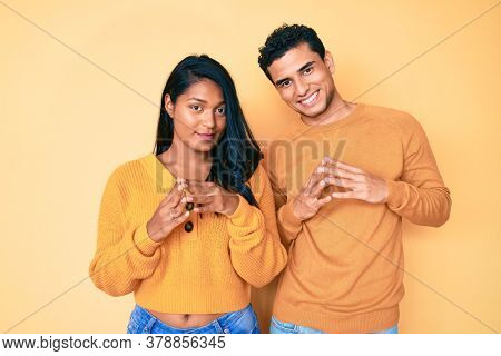 Beautiful latin young couple wearing casual clothes together hands together and fingers crossed smiling relaxed and cheerful. success and optimistic