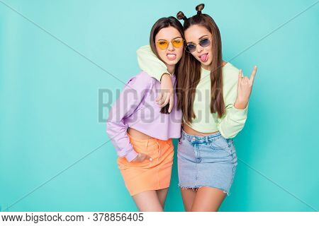 Photo Of Two Behavior Harsh Ladies Show Horns Hands Stick Tongue Out Mouth Wear Summer Sun Specs Gre