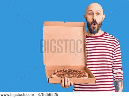 Young handsome man holding delivery pizza box scared and amazed with open mouth for surprise, disbelief face