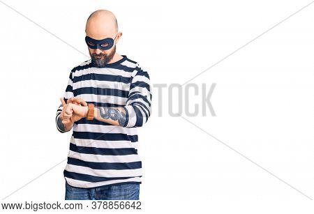 Young handsome man wearing burglar mask checking the time on wrist watch, relaxed and confident