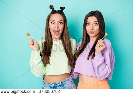 Photo Of Two Funny Cheerful Ladies Hold Lollipop Chupa Chups Hands Crazy Childish Mood Wear Cropped