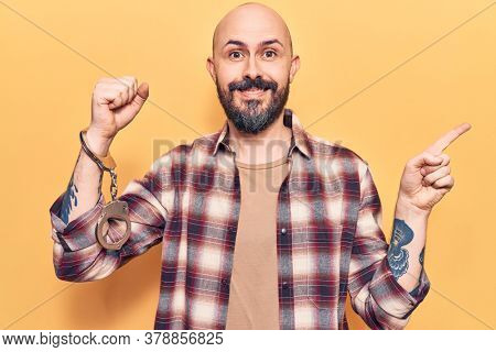 Young handsome man wearing prisoner handcuffs smiling happy pointing with hand and finger to the side