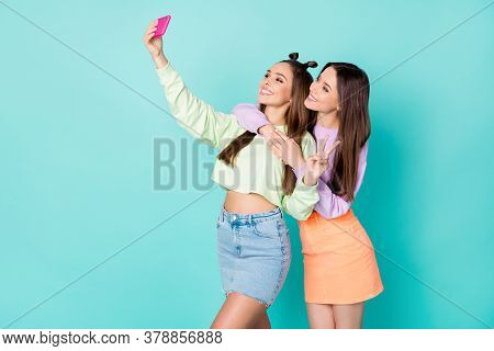 Photo Of Two Cheerful Ladies Best Friends Hold Telephone Take Selfies Showing V-sign Symbol Wear Cro