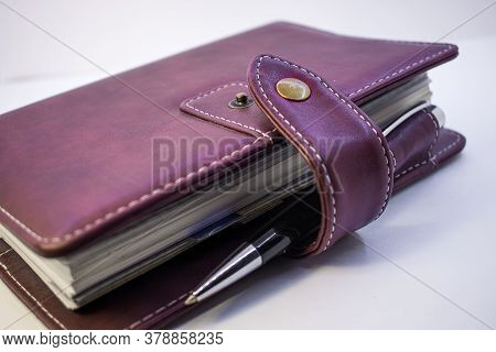A Maroon Notebook With An Iron Clasp Lies On A Light Background