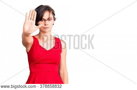 Beautiful young woman with short hair wearing casual style with sleeveless shirt doing stop sing with palm of the hand. warning expression with negative and serious gesture on the face.