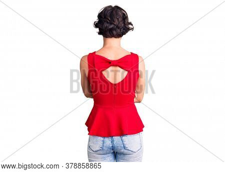 Beautiful young woman with short hair wearing casual style with sleeveless shirt standing backwards looking away with crossed arms