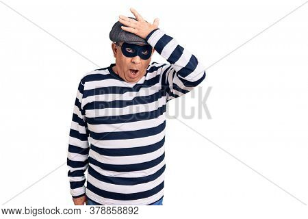 Senior handsome man wearing burglar mask and t-shirt surprised with hand on head for mistake, remember error. forgot, bad memory concept.