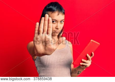 Young woman holding touchpad tablet with open hand doing stop sign with serious and confident expression, defense gesture