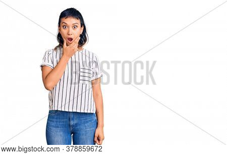 Young woman wearing casual clothes looking fascinated with disbelief, surprise and amazed expression with hands on chin