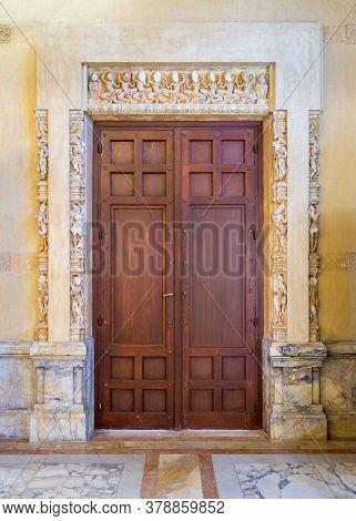 Closed Elegant Lumber Door Installed In Ornamental Archway Outside Of Old Marble Building