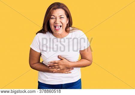 Middle age latin woman wearing casual white tshirt smiling and laughing hard out loud because funny crazy joke with hands on body.