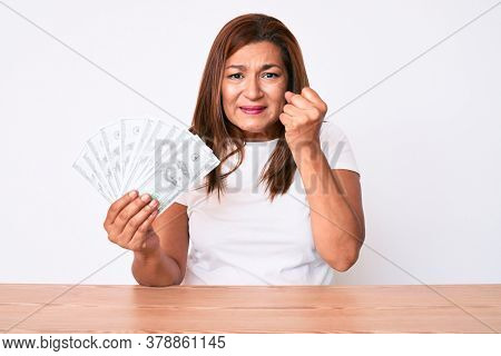 Middle age brunette woman holding dollars sitting on the table annoyed and frustrated shouting with anger, yelling crazy with anger and hand raised