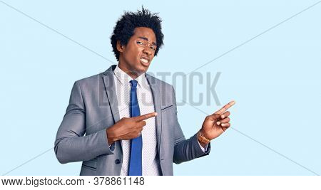 Handsome african american man with afro hair wearing business jacket pointing aside worried and nervous with both hands, concerned and surprised expression