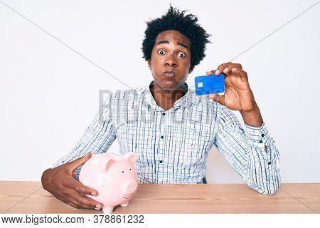 Handsome african american man with afro hair holding credit card and piggy bank puffing cheeks with funny face. mouth inflated with air, catching air.