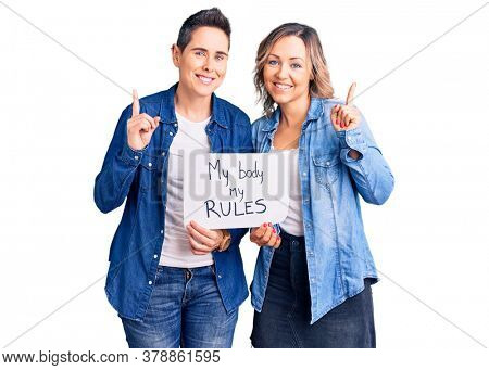 Couple of women holding my body my rules banner surprised with an idea or question pointing finger with happy face, number one