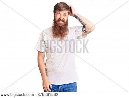 Handsome young red head man with long beard wearing casual white tshirt confuse and wonder about question. uncertain with doubt, thinking with hand on head. pensive concept.