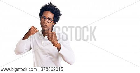 Handsome african american man with afro hair wearing casual clothes and glasses punching fist to fight, aggressive and angry attack, threat and violence