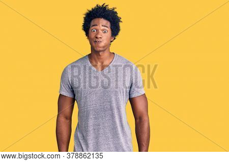 Handsome african american man with afro hair wearing casual clothes puffing cheeks with funny face. mouth inflated with air, crazy expression.