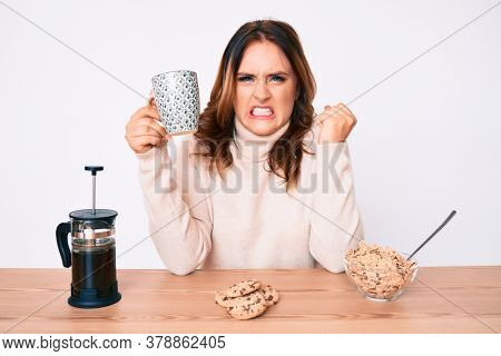 Young beautiful caucasian woman sitting on the table having breakfast annoyed and frustrated shouting with anger, yelling crazy with anger and hand raised