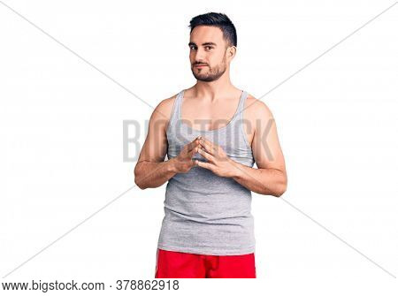 Young handsome man wearing swimwear and sleeveless t-shirt hands together and fingers crossed smiling relaxed and cheerful. success and optimistic