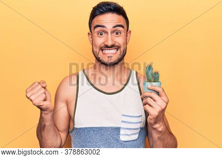 Young handsome man with beard wearing sleeveless t-shirt holding cactus plant pot screaming proud, celebrating victory and success very excited with raised arm