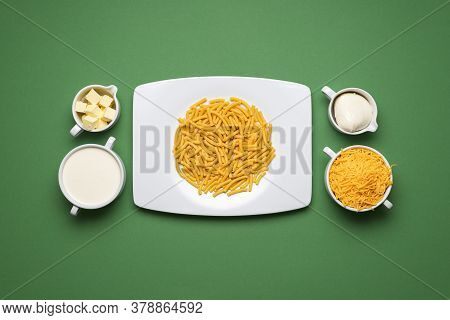 Uncooked Pasta And The Ingredients For Making Mac And Cheese. White Plate With Raw Macaroni On Green