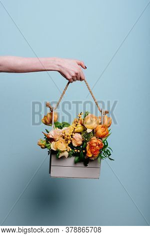 Bouquet Of Flowers In A Wooden Box In The Hand Of A Woman Florist On A Blue Background. Rosa Spray C