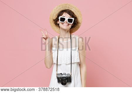 Smiling Young Tourist Woman In Summer Dress Hat Sunglasses With Photo Camera Isolated On Pink Backgr