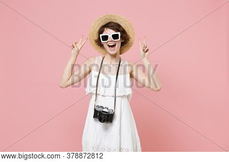 Cheerful Young Tourist Woman In Summer Dress Hat Sunglasses With Photo Camera Isolated On Pink Backg