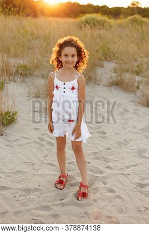 Frontal View Of A Little Cute Girl Posing At Sand On The Beach With A White Dress, Field Sunset Back