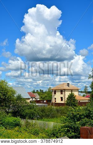 White Cumulus Clouds Float Across The Blue Sky Above The Houses. Beautiful Atmospheric Phenomenon. N