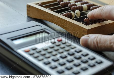 A Middle-aged Caucasian Man Makes Calculations On A Wooden Abacus. The Calculator Is Nearby. Close-u