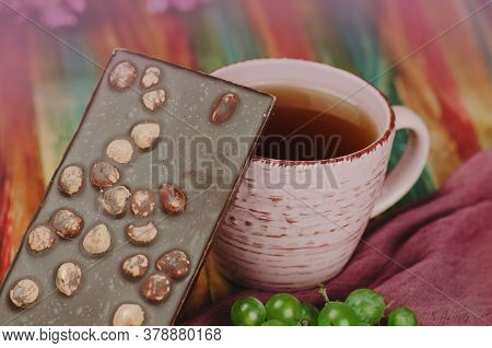 Chocolate With Hazelnut. Chocolate With Nuts And A Cup Of Tea
