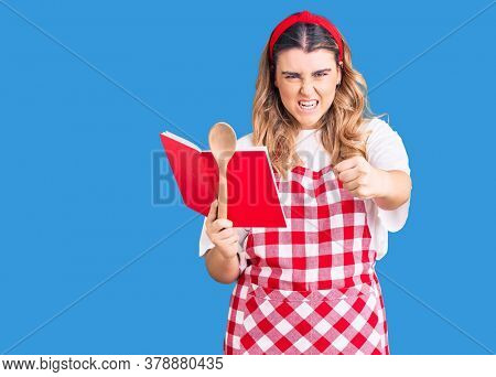 Young caucasian woman wearing apron holding recipe book and spoon annoyed and frustrated shouting with anger, yelling crazy with anger and hand raised