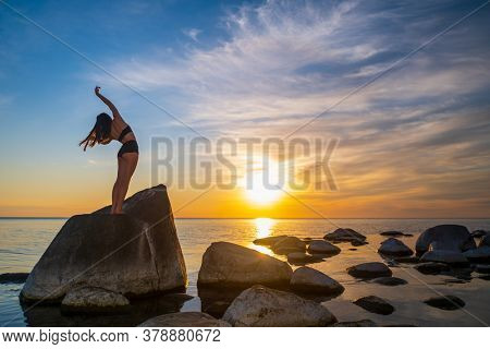 Back view of unrecognizable graceful woman bending aside with raised arms while dancing on stone near sea during sundown