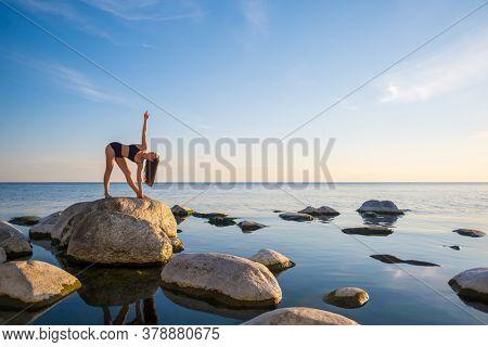 Full body slim woman in underwear standing on rock in Parivrtta Trikonasana pose while doing yoga near calm sea during sunset