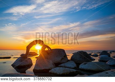 Side view of unrecognizable woman doing Wheel pose on boulders near sea against vibrant sunset sky