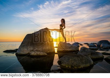 Side view of slim woman in underwear stretching legs on boulders against bright sundown sky in evening near sea
