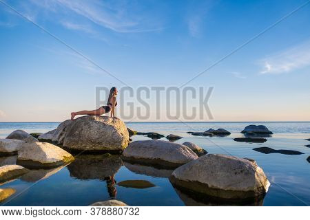 Side view of young woman in underwear doing Bhujangasana pose on stone while doing yoga on seashore during sunset
